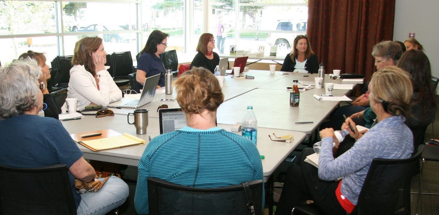 image of people sitting around a table at a book club meeting